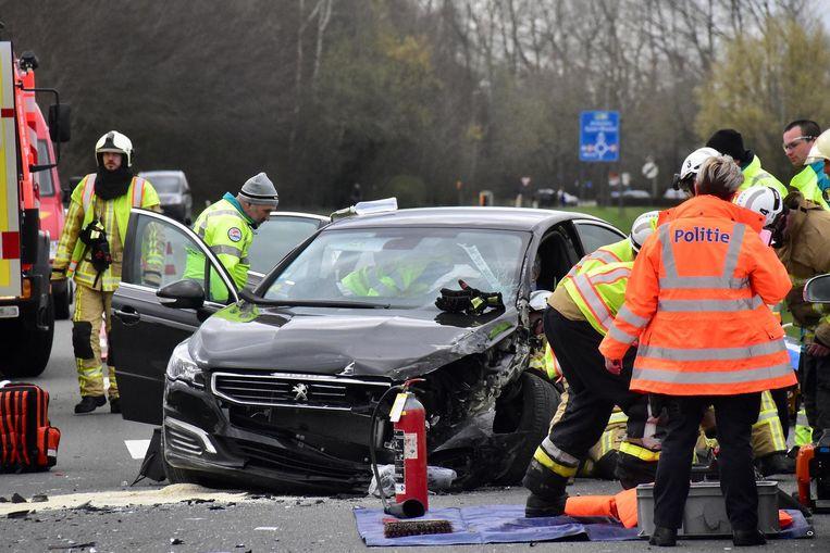 De hulpdiensten proberen de onfortuinlijke wagenbestuurder uit zijn benarde situatie te helpen.