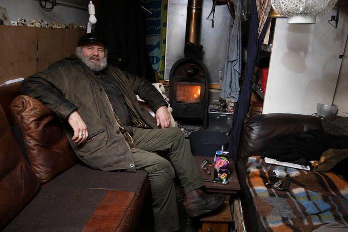 Henk Romein op de slaapbank voor de kachel in de omgebouwde kaasbus die als zijn woning dient.