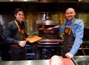 Rudi Seijdel en Fons Homan bereiden een stuk vlees in de houtoven.