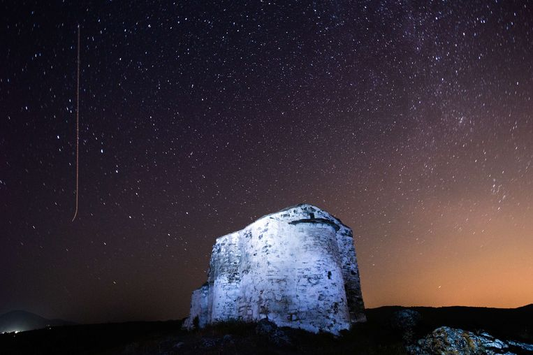 A long exposure image showing a Perseids meteor (L) streaking across the night sky over St. Ioan medieval church near the village of Potsurnentsi, late on August 12, 2013. The Perseid meteor shower occurs every year in August when the Earth passes through the debris and dust of the Swift-Tuttle comet.   AFP PHOTO / Dimitar DILKOFF Beeld AFP