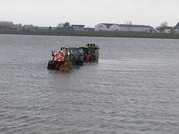 Drie trekkers rijden zich vast in water van de Boven-Merwede bij Werkendam.
