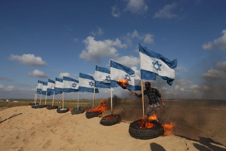 Een Palestijnse demonstrant steekt Israëlische vlaggen in brand bij de grens tussen Gaza en Israël, ten oosten van de stad Jabalia. Beeld AFP