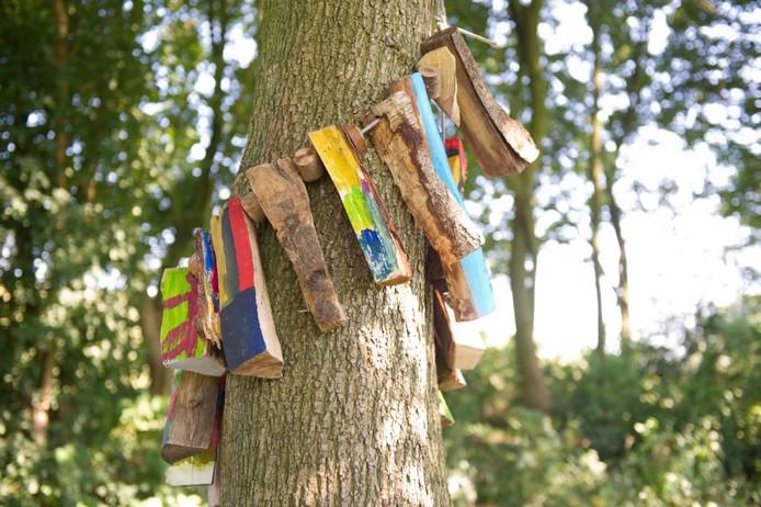De kinderen van BSO Op Stelten in Millingen maakten een vriendschapsketting door houtblokken als kralen aan een touw te rijgen. Ze bonden de ketting om deze twee in elkaar verstrengelde bomen.