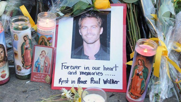 Fans van Paul Walker legden bloemen, foto's en kaarsen neer nabij de plaats van de crash in Californië. Beeld BELGA