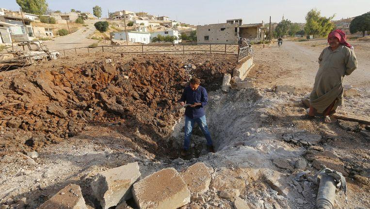 Inwoners in Latamneh, op het platteland van Hama, inspecteren een krater die is ontstaan na een Russische luchtaanval. Beeld reuters