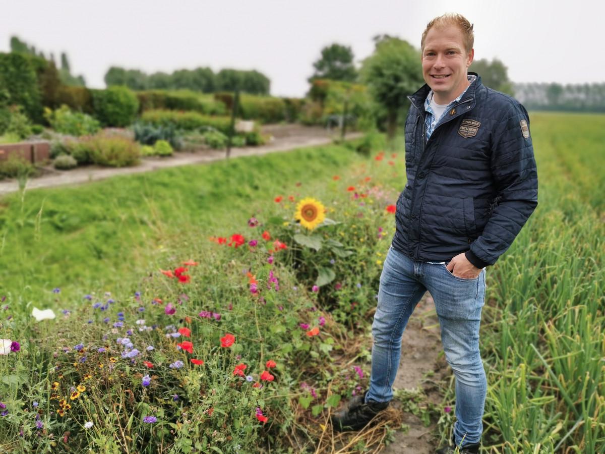 """Bart Brooijmans bij een akker die grenst aan een weg met huizen. """"Voor de bewoners veel leuker natuurlijk om uitzicht te hebben op de kleurrijke bloemen"""", zegt hij."""