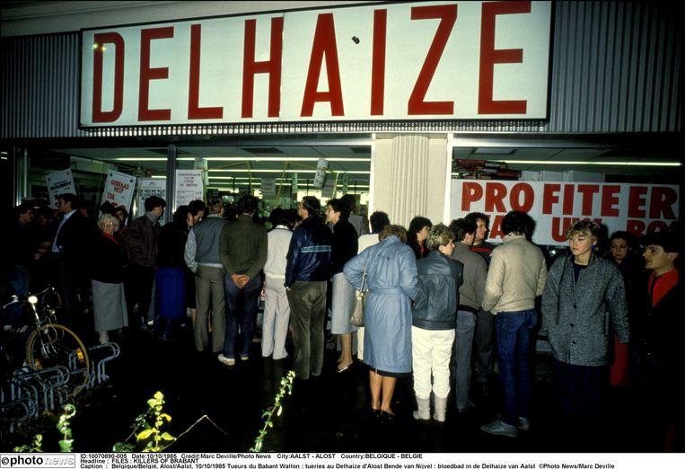 Omstanders verzamelen zich nabij de Delhaize in Aalst waar de Bende van Nijvel een dag eerder toesloeg, op 9 november 1985. Beeld Photo News