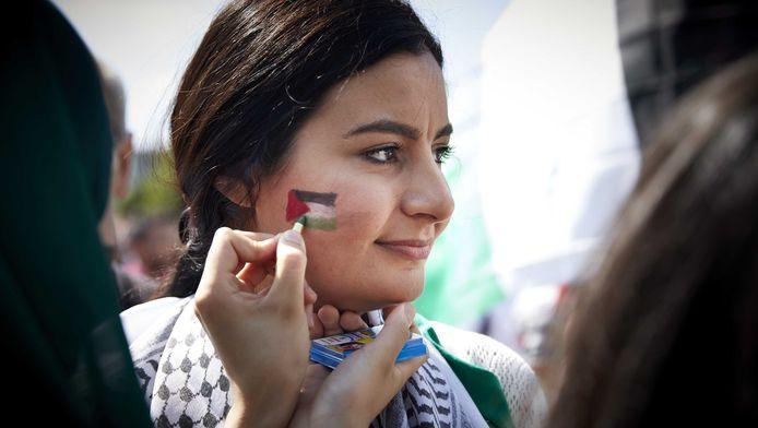 Een vrouw laat een Palestijnse vlag op haar gezicht tekenen tijdens een pro-Palestinademonstratie op het Museumplein in Amsterdam