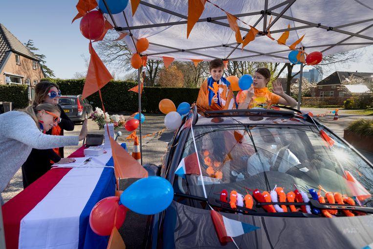Om er toch wat van te maken, organiseerde de Oranjevereniging van de Zwolse wijk Spoolde een tompouce drive-through.  Beeld Herman Engbers