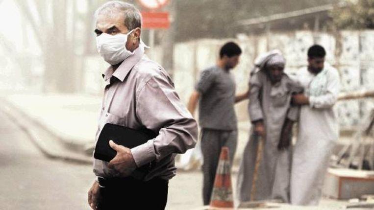 Een mondkapje tegen rondwaaiend zand en stof in Bagdad. (FOTO KARIM KADIM, AP) Beeld