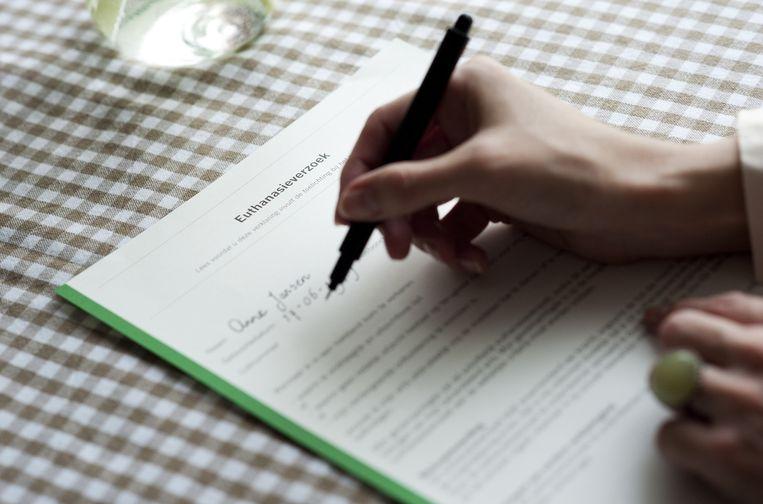 Een vrouw tekent een wilsverklaring, archiefbeeld. Beeld Anp