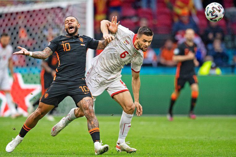 Memphis Depay wordt vastgehouden door Visar Musliu van Noord-Macedonië. Oranje won met 3-0. Beeld Guus Dubbelman / de Volkskrant