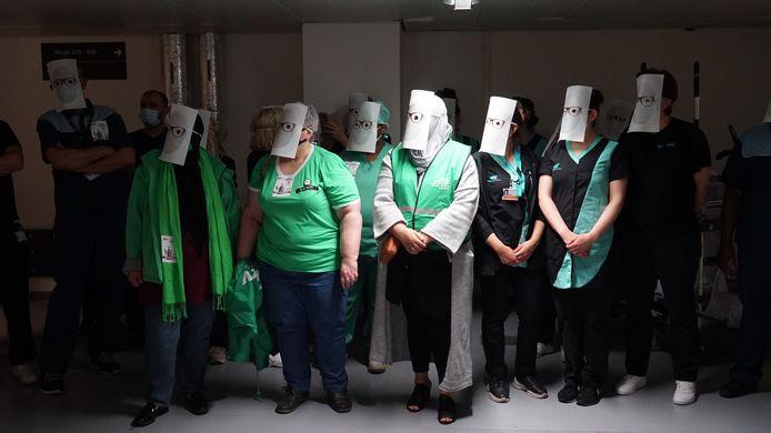 Zo'n veertig schoonmakers voerden actie in de kelders van het UZ Gent. Ze zetten een masker op omdat ze zich onzichtbaar en gediscrimineerd voelen ten opzichte van het vast personeel.