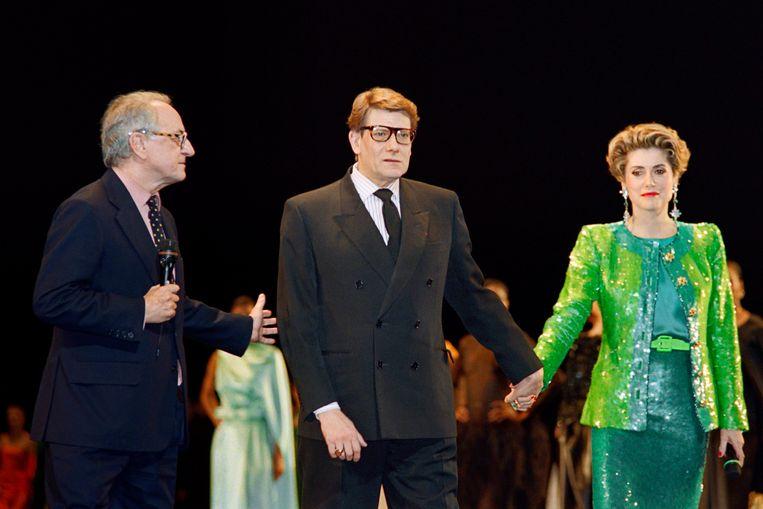 Pierre Bergé met Yves Saint Laurent en actrice Catherine Deneuve tijdens een modeshow ter ere van het 30-jarige modecarrière in februari 1992. Beeld AFP