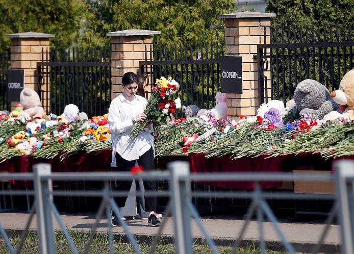 Molte persone vengono a deporre fiori e giocattoli nel santuario delle vittime all'ingresso della scuola.
