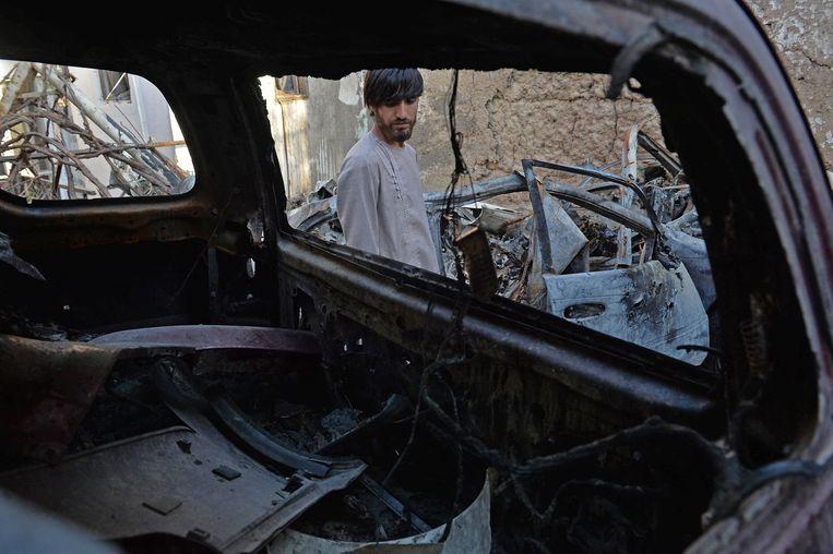 Een nabestaande bij de auto die de Verenigde Staten op 29 augustus vanuit een drone opbliezen. Het Amerikaanse leger dacht een terrorist van IS te doden, maar in werkelijkheid kwamen alleen tien burgers om, waaronder zeven kinderen. Beeld AFP