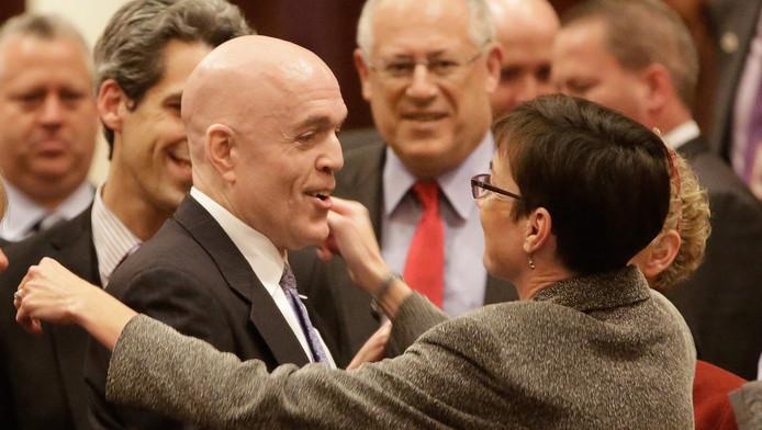 De Democratische Afgevaardigde Greg Harris (links) wordt gefeliciteerd nadat het Huis van Afgevaardigden in Illinois heeft ingestemd met het homohuwelijk.