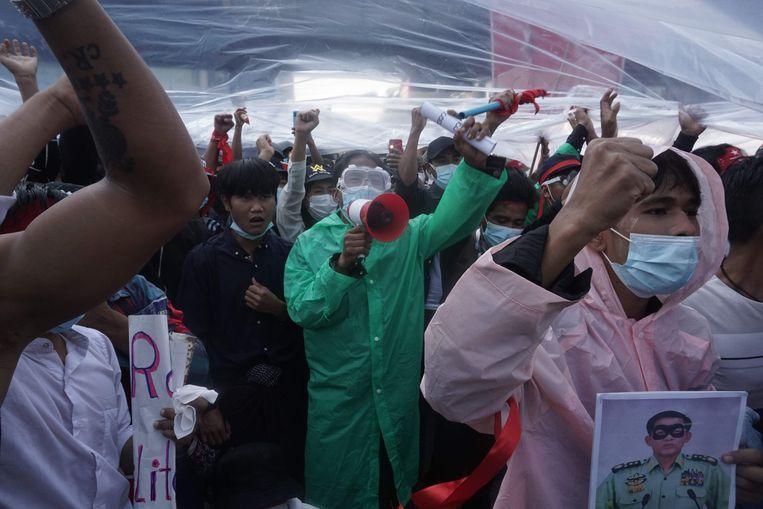 Demonstranten in regenpakken, als bescherming tegen de waterkanonnen die het leger inzet.  Beeld AFP