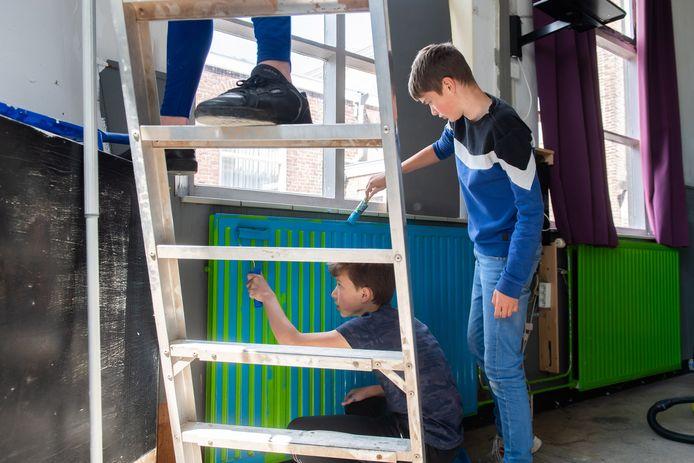 Zwaluwse jongeren klussen aan hun eigen nieuwe honk. Michel Vlachos (L) en Rik Beljaars schilderen de radiatoren blauw.