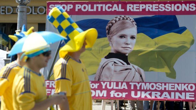 Zweedse voetbalsupporters voor een poster waarop wordt opgeroepen tot het vrijlaten van Timosjenko, vandaag in Kiev. Beeld ap