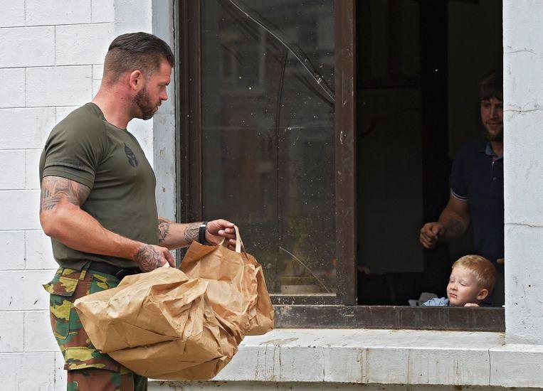 Een militair die eten uitdeelt in Pepinster. Beeld Photo News