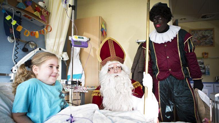 De 7-jarige Adriana krijgt bezoek van Sinterklaas en Zwarte Piet aan haar bed in het Wilhelmina Kinderziekenhuis in Utrecht Beeld ANP