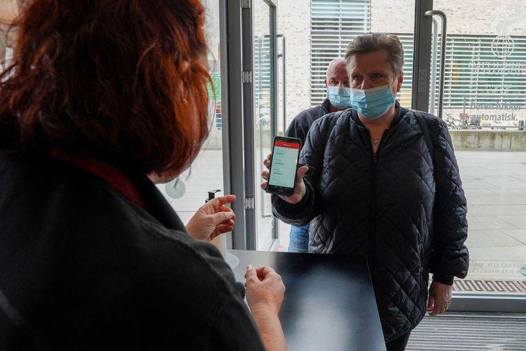 Een bezoeker toont zijn coronapas voor hij de cinema binnenkomt in Denemarken. Beeld AFP