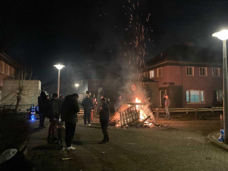 In Floradorp staan buurtbewoners rond een geïmproviseerd oudejaarsvuur. Beeld Hannah Stöve