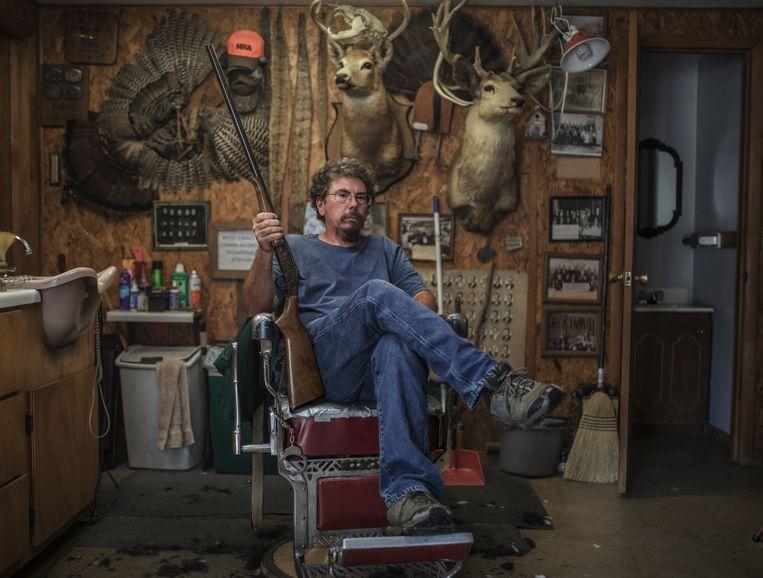 Mark Eileff (52) in zijn kapperszaak, met een geweer in zijn handen en omringd door jachttrofeeën. Volgens Eileff begrijpt zelfs zijn negenjarige dochter dat 'ons land er echt slecht aan toe is'.  Beeld © Espen Rasmussen/Verdens Gang/Panos Pictures