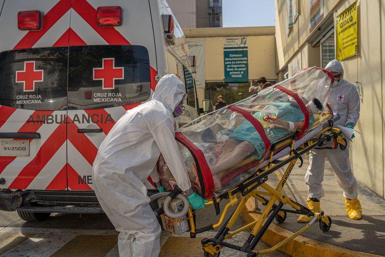 Medewerkers van het Rode Kruis brengen een coronapatiënt naar een ander ziekenhuis in Mexico-Stad. Beeld Alejandro Cegarra