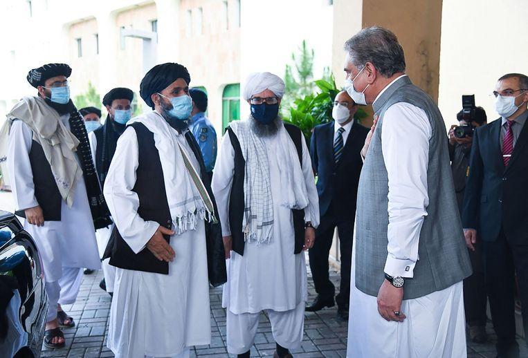 De Pakistaanse minister van buitenlandse zaken (r) groet een Taliban-delegatie in 2020.  Beeld AFP
