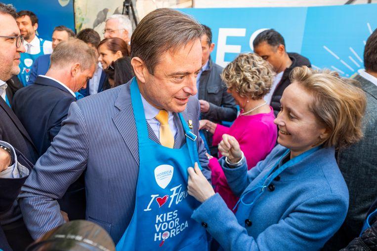 Schepen Annick De Ridder helpt de burgemeester bij het aandoen van zijn schort. N-VA zegt duidelijk voorstander te zijn van de flexi-jobs.