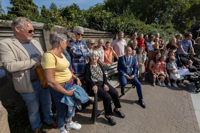 Toos Snellen-van Beek zit - omringd door familie en bekenden - samen met burgemeester Anton Ederveen op het zojuist onthulde bankje op het Kloosterplein in Valkenswaard.