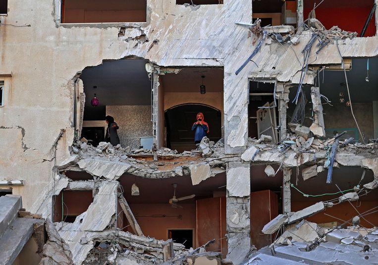 Palestijnse vrouwen nemen de schade op aan een gebouw in Gazastad, na Israëlische bombardementen.  Beeld AFP