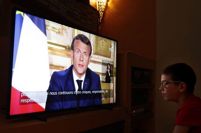 Een jongen bekijkt de persconferentie van president Macron in zijn huiskamer.
