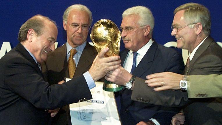 Horst Schmidt (uiterst rechts) neemt de wereldbeker in ontvangst van FIFA-baas Sepp Blatter (uiterst links) na het binnenhalen van het WK 2006. Verder op de foto Franz Beckenbauer (tweede van links) en Fedor Radmann, een andere grote man achter het bid van Duitsland. Beeld AP