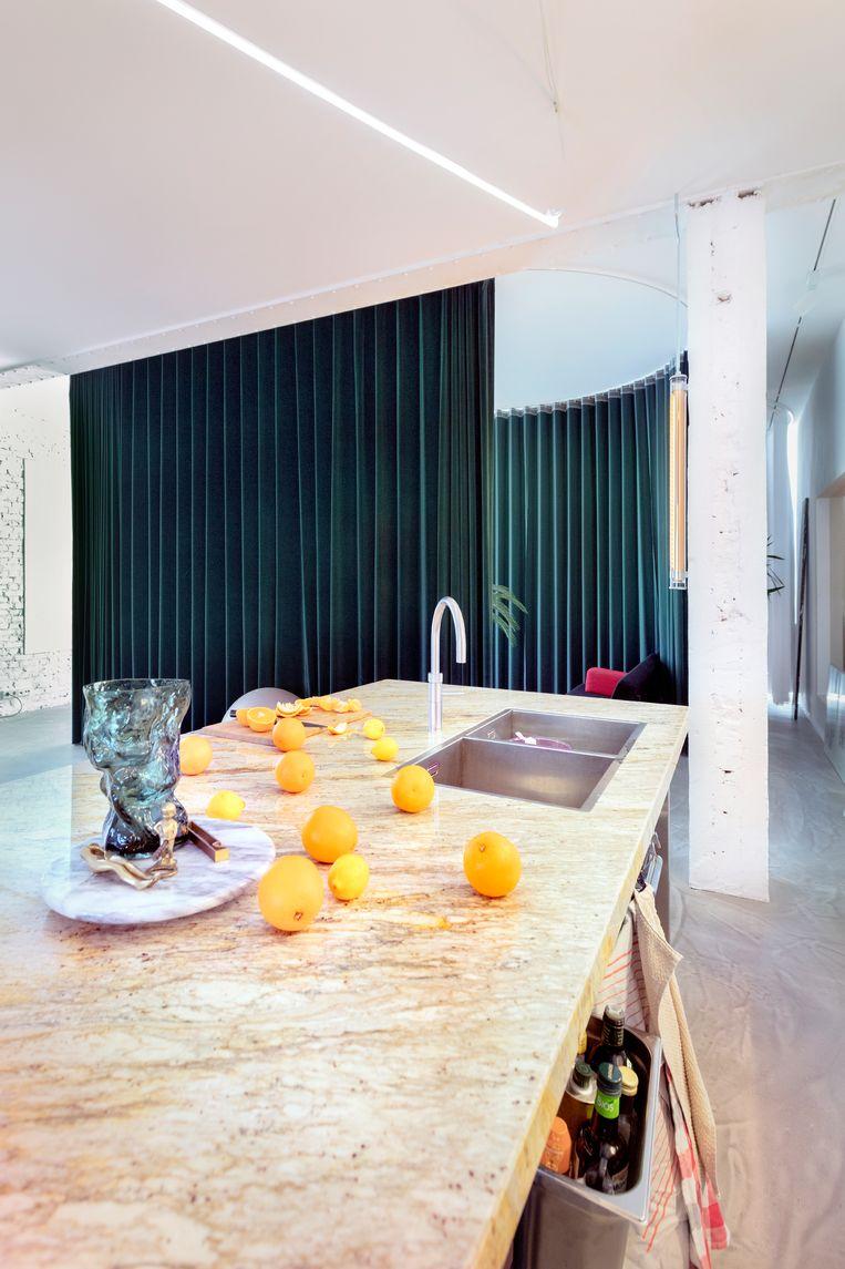 In de keuken hebben we neonverlichting gecombineerd met lampen van het Franse merk Sammode.'  'De draaischotel is een Lazy Susan van mijn grootouders. De vaas die erop staat, is van de kunstenaar Fos, ontworpen voor het modehuis Céline.' Beeld Marleen Sleeuwits