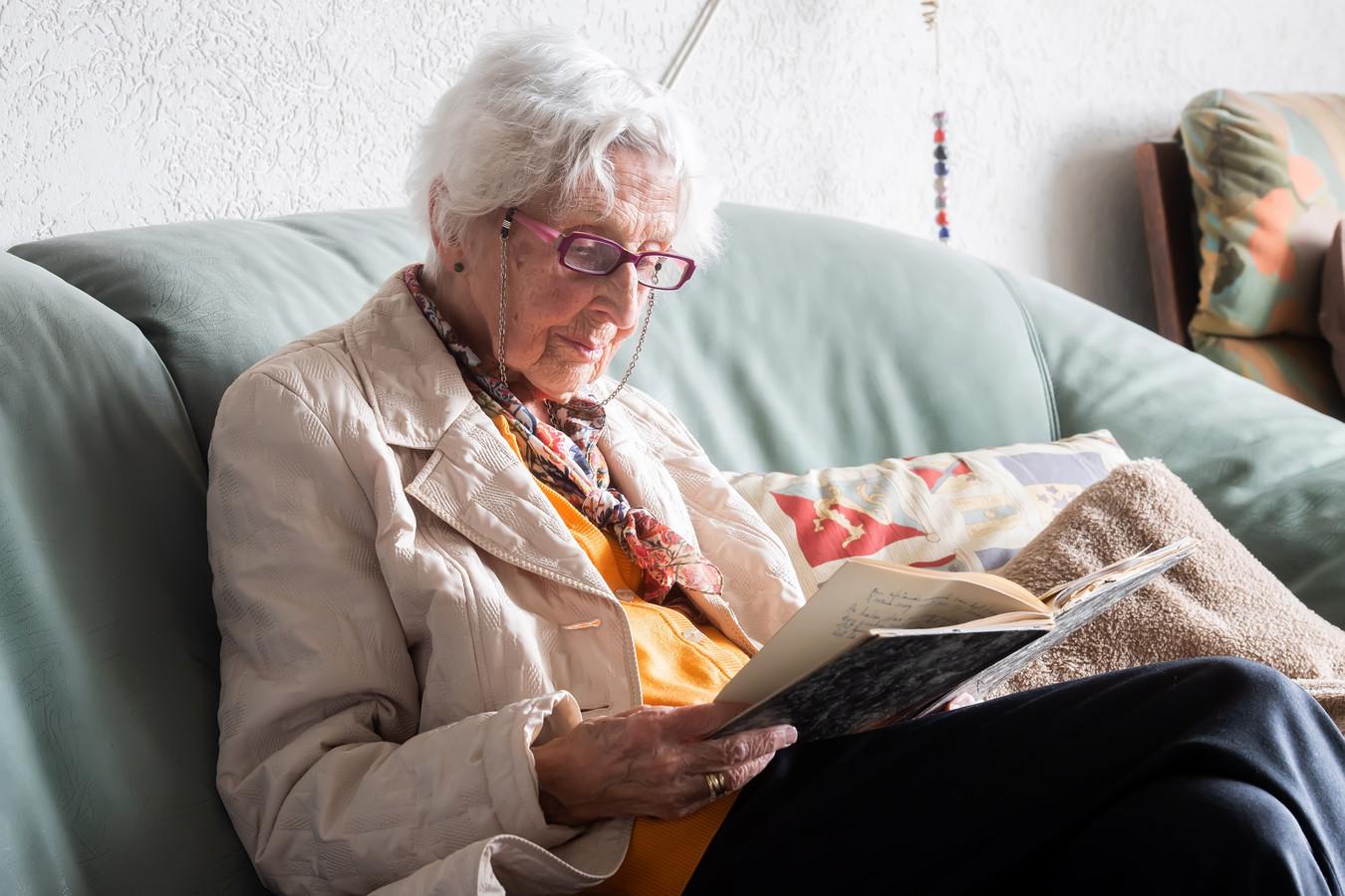 Wies Wolf-Dekkers bladert in één van haar oude plakboeken.