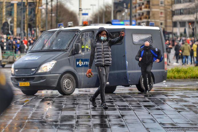 Relschoppers gooien stenen naar de politie.