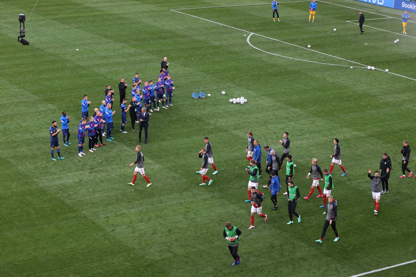 De Finnen klappen voor de Denen als die ze na een pauze van ruim anderhalf uur terugkeren voor de hervatting van het EK-duel.