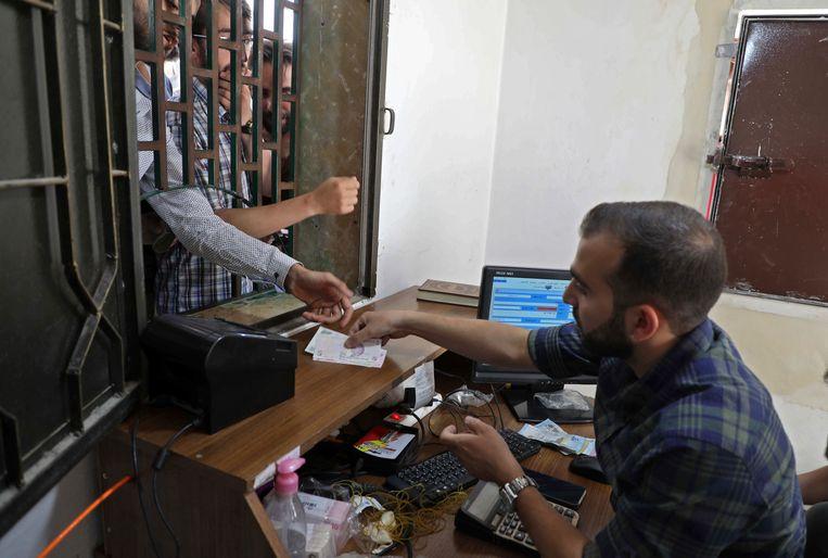 Een Syrische man ontvangt een Turkse lira bij een wisselkantoor in Sarmada.  Beeld AFP