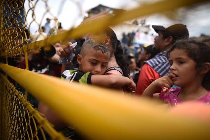 Een grote stoet migranten werd bij een van de bruggen over de Suchiate rivier tegengehouden. De brug is een natuurlijke grens tussen Guatemala en Mexico.