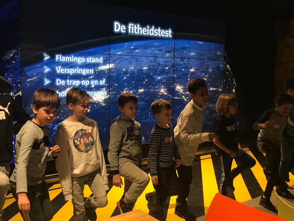Leerlingen van de Ruimtevaartschool in de LocHal doen een evenwichtsoefening.