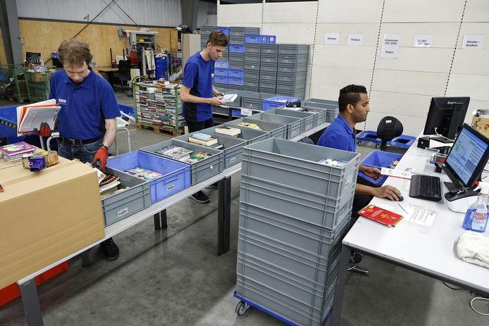 Medewerkers van Vindingrijk sorteren boeken.