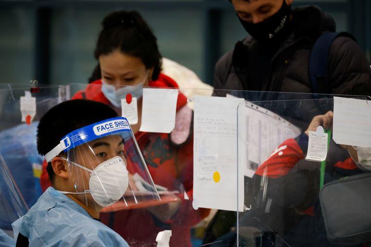 Een vrouw checkt aankomende passagiers op de internationale luchthaven van Incheon, Zuid-Korea. Beeld REUTERS