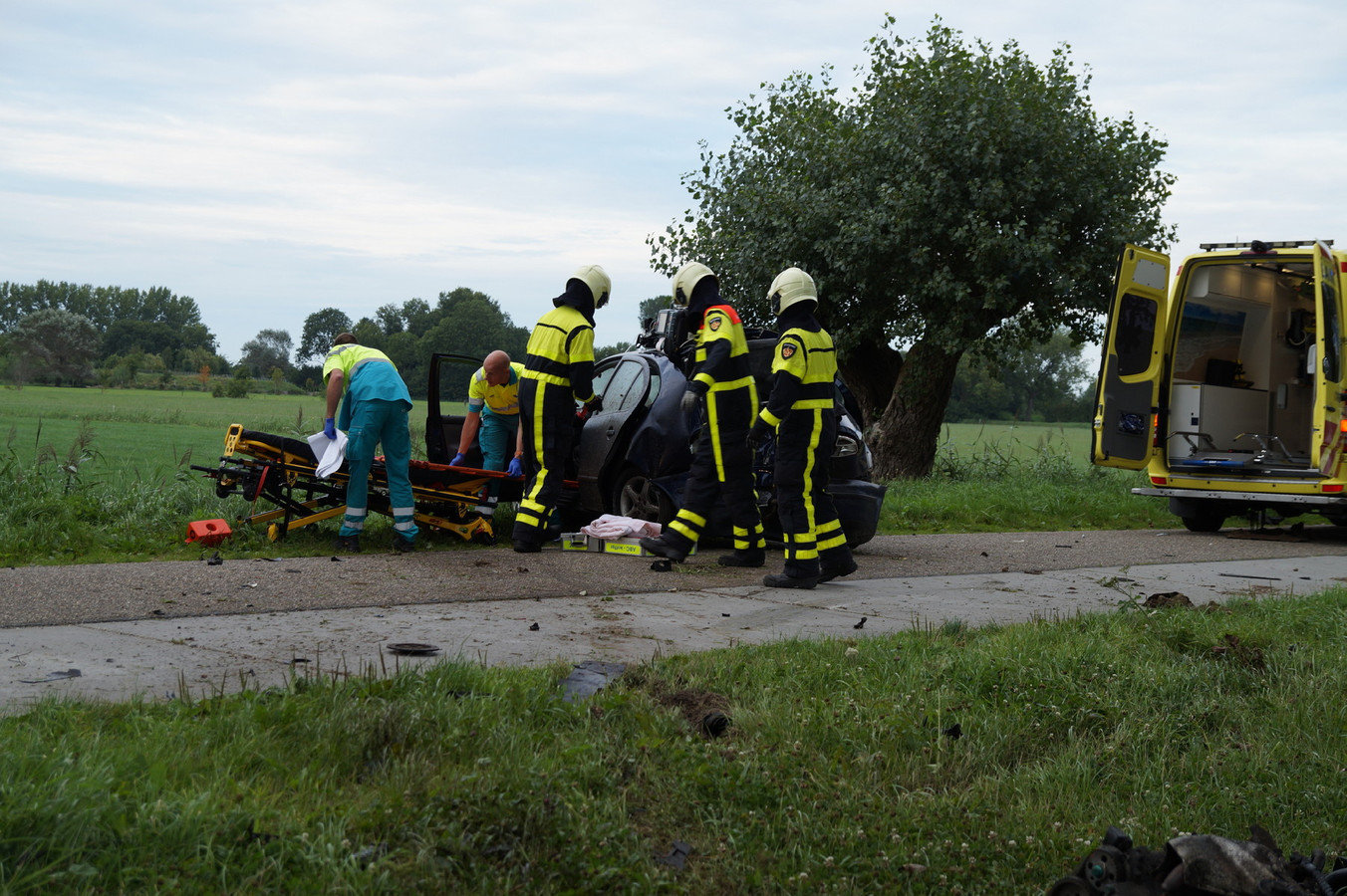 De man is door ambulancepersoneel uit de auto gehaald.