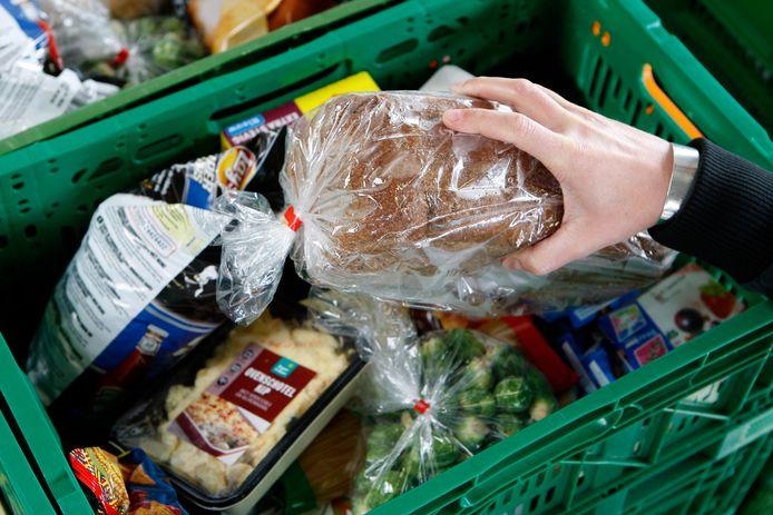 2008-10-02 00:00:00 DEN HAAG - Medewerkers van de Voedselbank in Den Haag stellen de voedselpakketten samen. De Voedselbank schenkt de voedselpakketten aan mensen die beneden het bestaansminimum leven. De mensen kunnen de pakketten ophalen bij uitdeelposten of thuisbezorgd krijgen. De Voedselbank zamelt bij producenten en distributeurs van levensmiddelen de producten in die om een of andere reden niet verkocht kunnen worden, maar die kwalitatief nog honderd procent goed zijn. ANP PHOTO XTRA KOEN SUYK