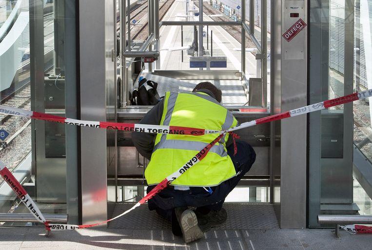 Een monteur repareert een stationslift. De NS staat open voor asielzoekers. Beeld  HH