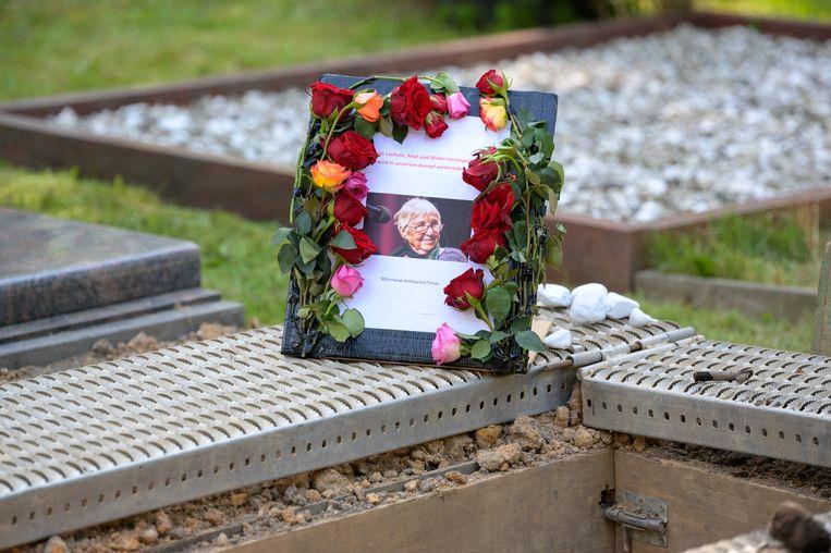 Naast het graf van Esther Bejarano staat een lijst met haar foto. Holocaustoverlevende Bejarano, die in concentratieklamp Auschwitz zat, werd 96 jaar oud. Ze werd gisteren begraven op de Joodse begraafplaats van Hamburg. f Beeld Jonas Walzberg/dpa-Pool/dpa