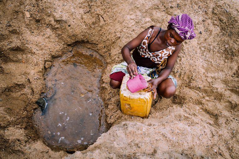 De aangetroffen foto's tonen onder meer een vrouw die op de bodem van de uitgedroogde Manambovo-rivier bij de plaats Tsihombe een put heeft geslagen om haar jerrycan met water te vullen.  Beeld Reuters